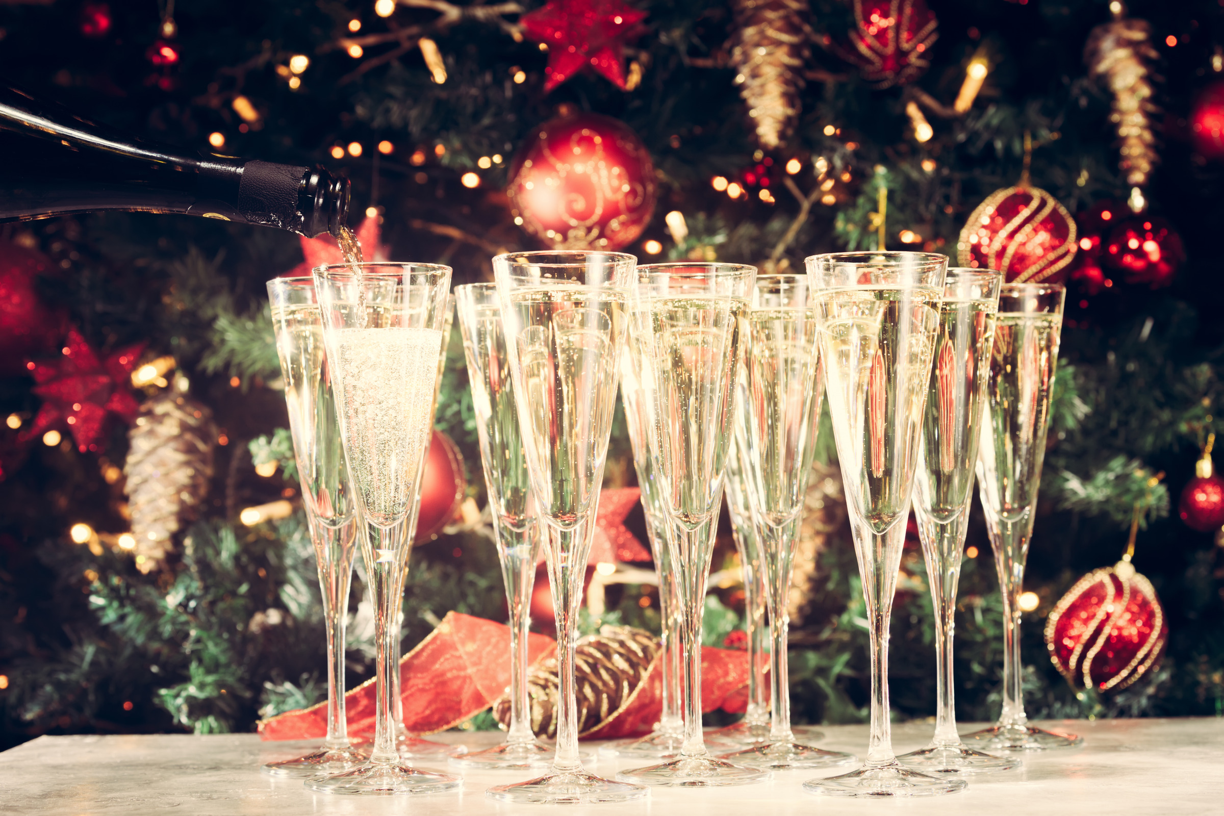 Filling up glasses for party. Many glasses of champagne with Christmas tree background. Party setup. Holiday season background. Traditional red and green Christmas decoration with lights. Holiday party. Horizontal